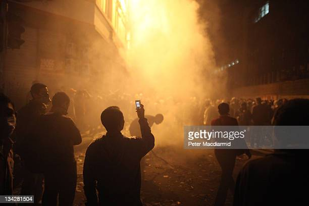 A youth films the aftermath of a tear gas volley fired by police on protestors in Muhammed Mahmoud Street near Tahrir Square on November 23 2011 in...