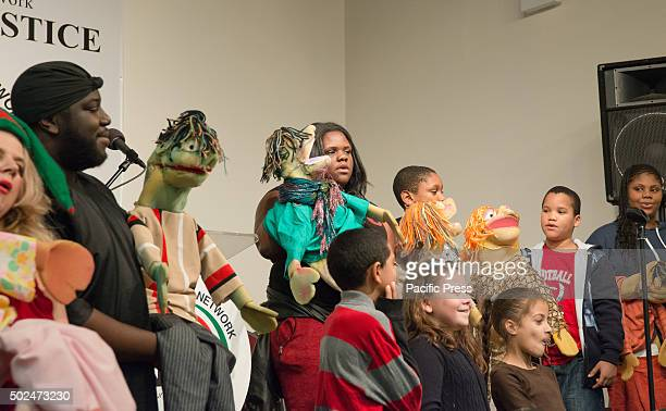 A youth group at the National Action Network perform with puppets while singing Christmas carols New York City Mayor Bill de Blasio and his daughter...