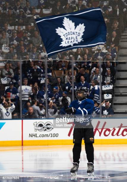 A youth hockey player waves a Toronto Maple Leafs flag before the Leafs face the Washington Capitals in Game Six of the Eastern Conference First...