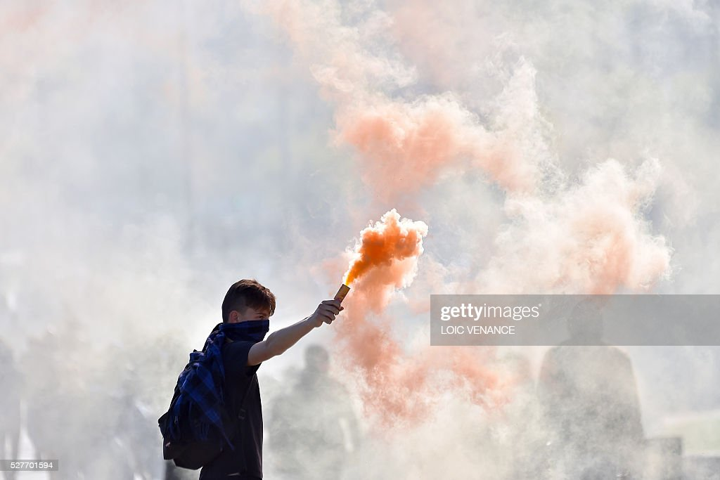 A youth holds a flare during a protest against the government's planned labour law reforms in Nantes, western France, on May 3, 2016. High school pupils and workers protested against deeply unpopular labour reforms that have divided the Socialist government and raised hackles in a country accustomed to iron-clad job security. / AFP / LOIC