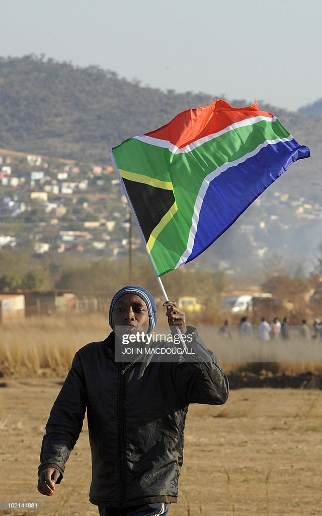 A youth holds a South African flag as he walks across a makeshift football field outside the Atteridgeville township near Pretoria June 16, 2010 as the 2010 World Cup is being held in South Africa.