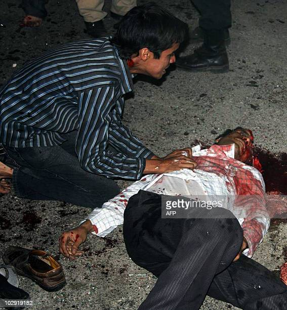 A youth inspects the body of a victim outside the Jameh mosque in the southeastern Iranian city of Zahedan on July 15 2010 Two suicide bombings at a...