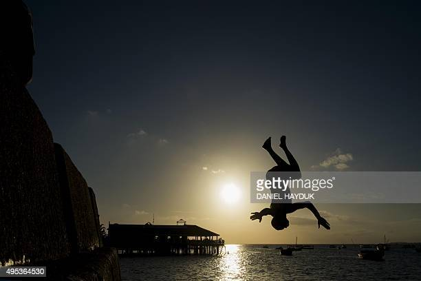 A youth jumps into the Indian Ocean at the water front of the historical Stone Town of Zanzibar on November 2 2015 AFP PHOTO / DANIEL HAYDUK