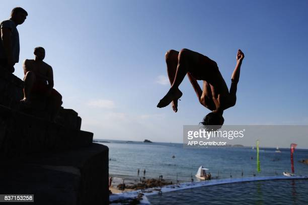 TOPSHOT A youth jumps into the water at a beach in Dinard northwestern France on August 22 2017 / AFP PHOTO / CHARLY TRIBALLEAU
