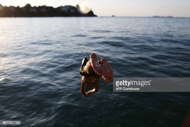 TOPSHOT A youth jumps into the water at a beach in Dinard northwestern France on August 22 2017 TRIBALLEAU