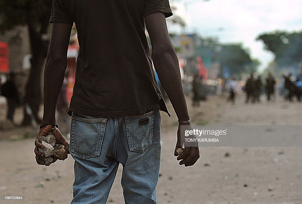 A youth of non-Somali ethinicity armed with stones stands on November 19, 2012 during inter-ethnic clashes in Nairobi's Eastleigh suburb. Clashes broke out a day after a bomb exploded in a minibus, blamed on sympathisers of Somalia's Al-Qaeda-linked Shebab insurgents, killing seven people and leaving several wounded. A day after the blast, non-Somali Kenyans turned on Somalis and attacked their shops and stalls, accusing them of being responsible for the bomb. No one has claimed responsibility for the blast. AFP PHOTO / Tony KARUMBA