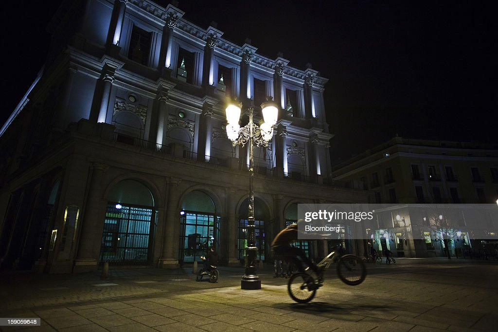 A youth performs stunts on a bicycle beneath an electric street light outside the Royal theatre in Madrid, Spain, on Sunday, Jan. 6, 2013. In December, the Spanish parliament passed an energy law that imposed a 7 percent tax on electricity generation from Jan. 1 to plug the deficit. Photographer: Angel Navarrete/Bloomberg via Getty Images