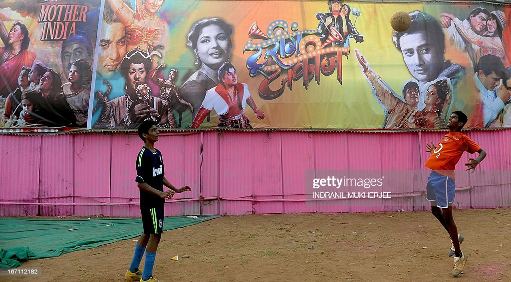 Youth play a game of football in front of a poster collage of various Indian movies put up to decorate the boundary wall of the Anup Touring Talkies tent cinema at a ground in central Mumbai on April 19, 2013. To mark 100 years of Indian Cinema, a Marathi film 'Touring Talkies' is being screened in a makeshift tent theatre just like the days of yore, in its pre-multiplex and pre-single screen glory dating back 50 years. The tents, keeping in mind modern audiences, will have plush seating, air conditioning and popcorn and cola alongside fresh sugar-cane juice, roasted groundnuts and gram and pickle and other tit-bits. The cinema will screen four shows per day for a week. The idea of touring talkies was the brainchild of the doyne of Indian cinema, Dadasaheb Phalke, after he saw the British watching movies in tents. The touring cinema would travel through rural India and screen movies in makeshifts tents. At present, one can only find these talkies - whose sweltering tents and basic facilities contrast with the plush, air-conditioned multiplexes springing up in Indian cities, during Jatras (village fairs) in the interiors of the state. AFP PHOTO/ INDRANIL MUKHERJEE