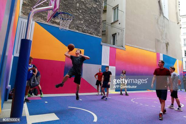 Youth play basketball at the Duperre Pigalle playground in Paris on June 29 2017 / AFP PHOTO / Benjamin Cremel