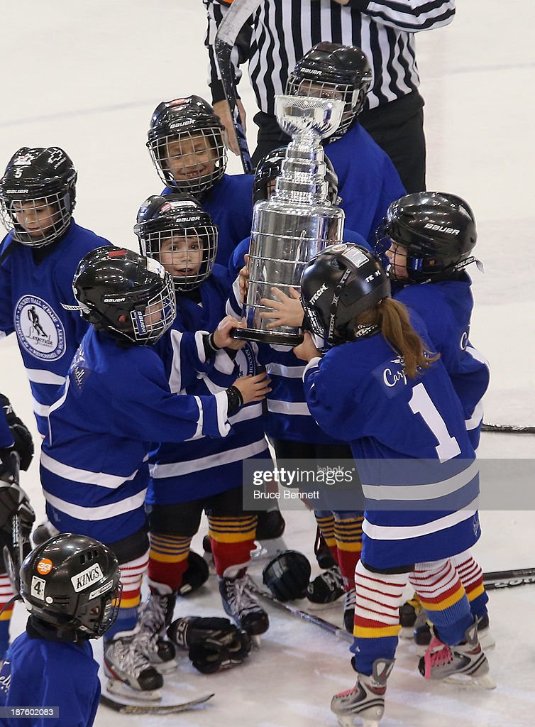 Youth players carry an imitation Stanley Cup during a break in the 2013 Hockey Hall of Fame Legends Classic game at the Mattamy Athletic Center on November 10, 2013 in Toronto, Canada.
