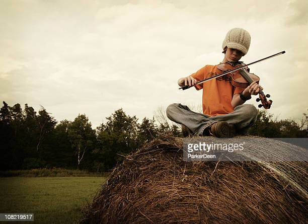 Youth playing a fiddle on top of a giant hay bale