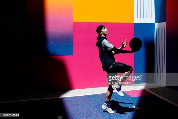 A youth plays basketball at the Duperre Pigalle playground in Paris on June 29 2017 / AFP PHOTO / Benjamin Cremel
