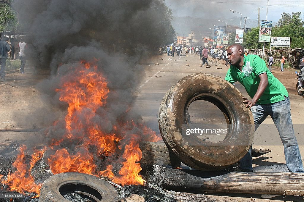 A youth prepares on October 29, 2012 to burn a tyre along a road in the western Kenyams lakeside town of Kisumu during riots that followed the murder of a prominent local politician. Violent protests erupted after Shem Onyango Kwega, a candidate for a parliamentary seat in Kisumu in general elections due in March, was killed by unidentified armed men on October 30 while driving in town. Kwega, the local branch chairman of Prime Minister Raila Odinga's Orange Democratic Movement (ODM), was shot in the head and later died at the hospital while his wife was seriously wounded in the same attack. Four people were wounded by bullets during confrontations with the police and a police officer was hit by a stone hurled by the protesters.