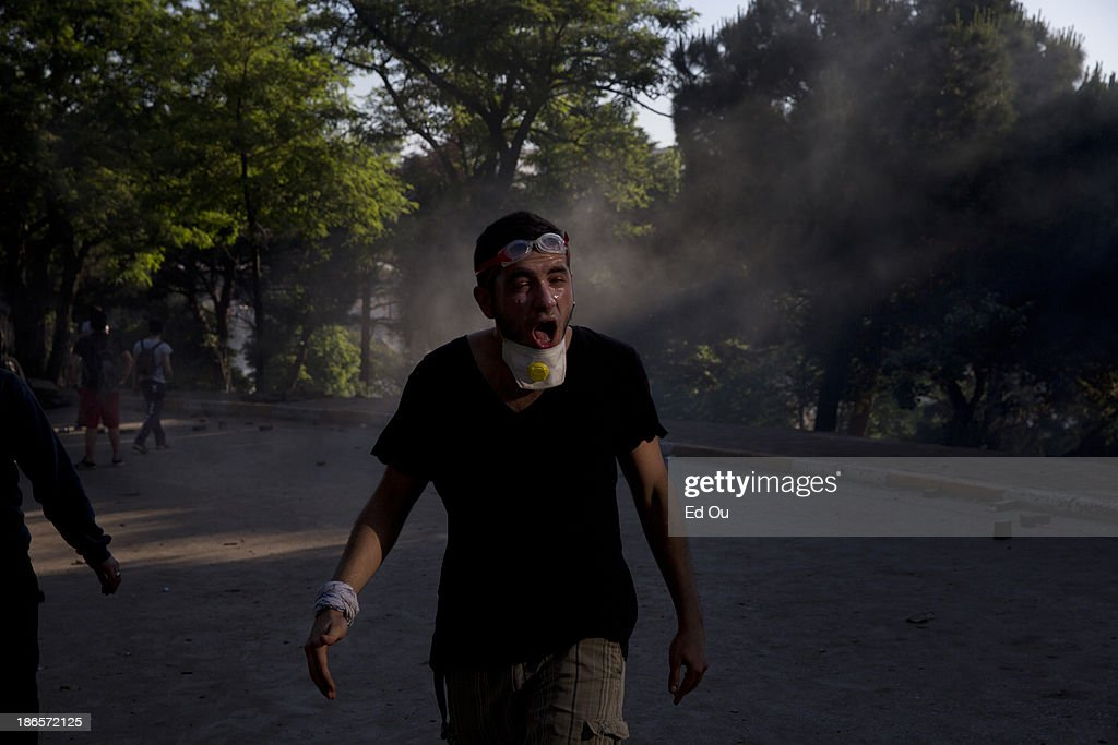 A youth protester gasps for air after being inundated by tear gas during a clash with police in a back and forth scuffle as his group holds a...