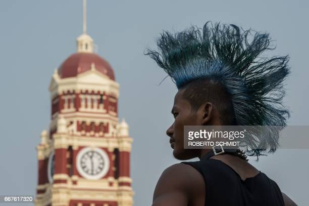 A youth punk stands in a park near a 1900's colonial era former High Court building in Yangon on April 12 2017 on the eve of the water festival known...