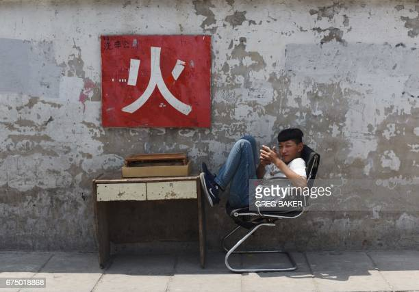 TOPSHOT A youth rests on a chair outside a car wash in Beijing on April 30 2017 The Chinese character on the wall says 'fire' which forms part of a...