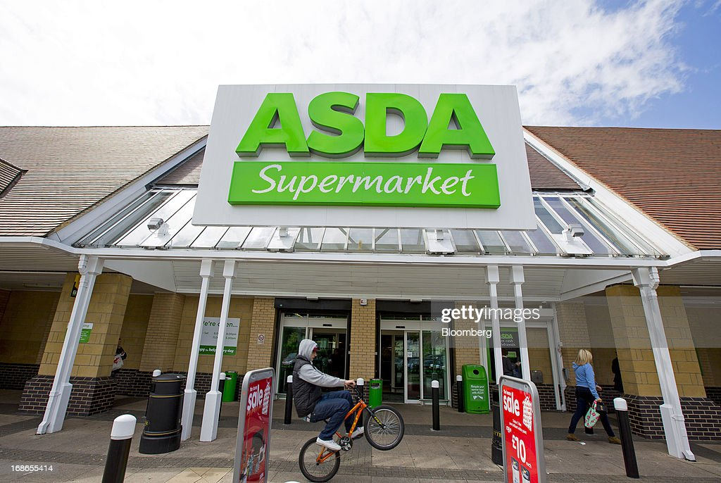 A youth rides a BMX bicycle past the entrance to an Asda supermarket store, operated by Wal-Mart Stores Inc., in the Richmond-upon-Thames borough of London, U.K., on Monday, May 13, 2013. Asda, the U.K. supermarket chain owned by Wal-Mart Stores Inc., said sales rose 4.5 percent last year and it's investing 700 million pounds ($1 billion) into stores and online operations. Photographer: Jason Alden/Bloomberg via Getty Images