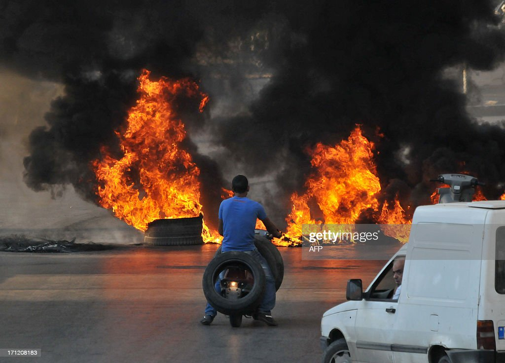 A youth rides his moped as he carries tires towards a burning barricade across a street in the northern city of Tripoli, on June 23, 2013, during protests in support of Sunni Muslim Sheikh Ahmad al-Assir whose supporters have clashed with the Lebanese army in the southern Lebanese city of Sidon. Two Lebanese army officers and a soldier were killed in the clash with supporters of the radical Sunni Muslim Sheikh opposed to the powerful Shiite movement Hezbollah, an army statement said. AFP PHOTO / IBRAHIM CHALHOUB