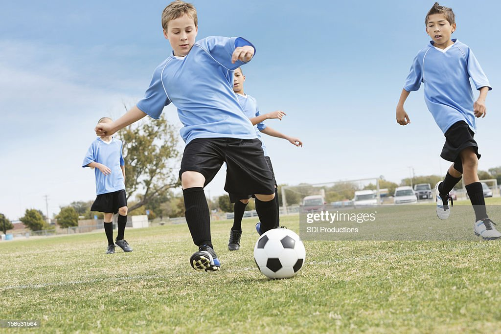 Youth soccer team kicking ball during game : Stock Photo
