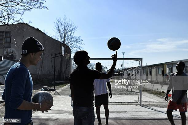 TOPSHOT A youth spins a ball before a match of football at the Elaionas camp for migrants and refugees in Athens on January 28 2016 More than a...