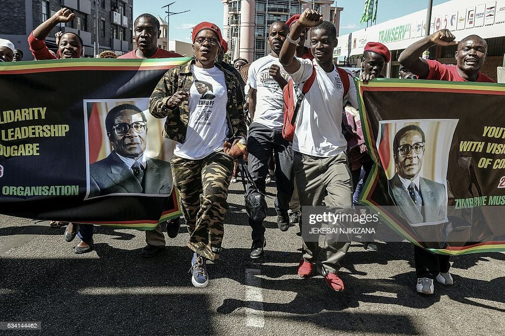 Youth Supporters of Zimbabwean President cheer during the Zimbabwe African National Union Patriotic Front 'One Million Youth March' on May 25, 2016 in Harare. Several thousand Zimbabweans joined a march through Harare in support of veteran President Robert Mugabe after the main opposition party staged its own rally last month. / AFP / Jekesai Njikizana