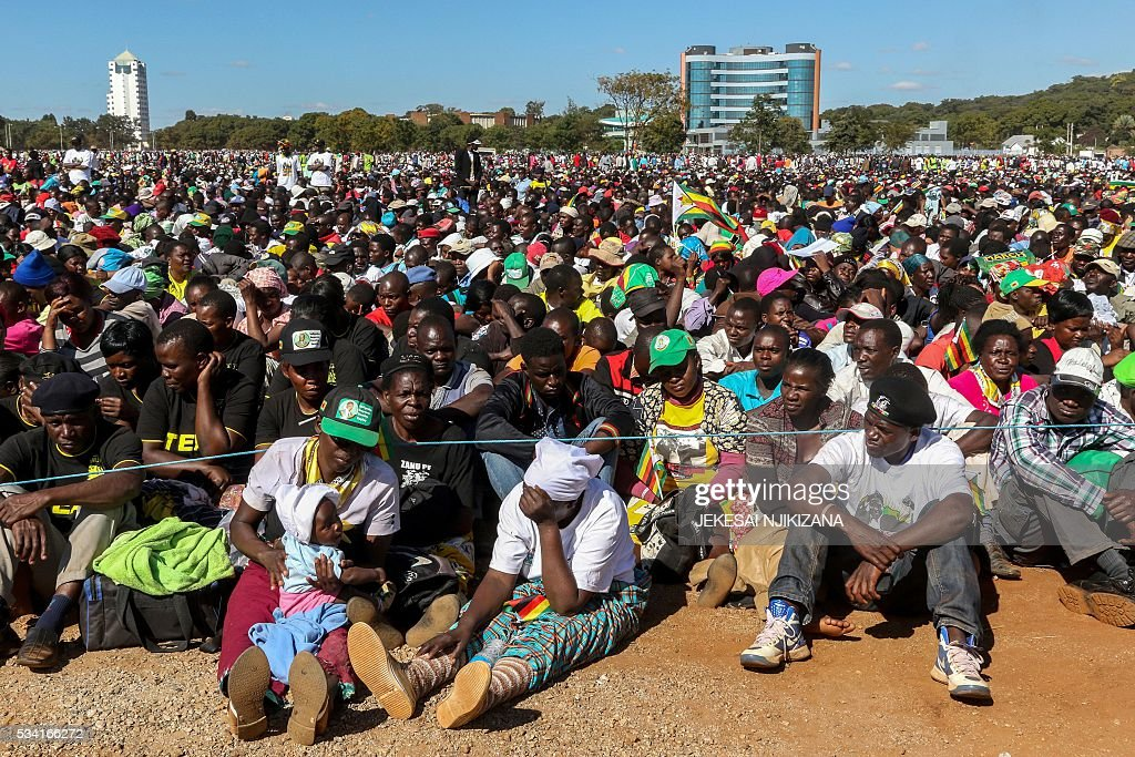 Youth Supporters of Zimbabwean President Robert Mugabe listen to his speech during the Zimbabwe African National Union Patriotic Front 'One Million Youth March' on May 25, 2016 in Harare, Zimbabwe. Several thousand Zimbabweans joined a march through Harare in support of veteran President Robert Mugabe after the main opposition party staged its own rally last month. The marchers sang songs praising Mugabe and wore t-shirts displaying his image as they gathered at a central park to hear his 90-minute speech. / AFP / Jekesai Njikizana