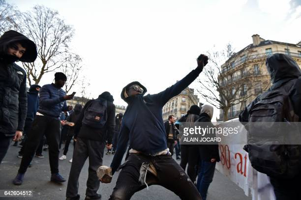 A youth throws a rock at antiriot police officers during a demonstration against police brutality on February 18 2017 on the place de la Republique...