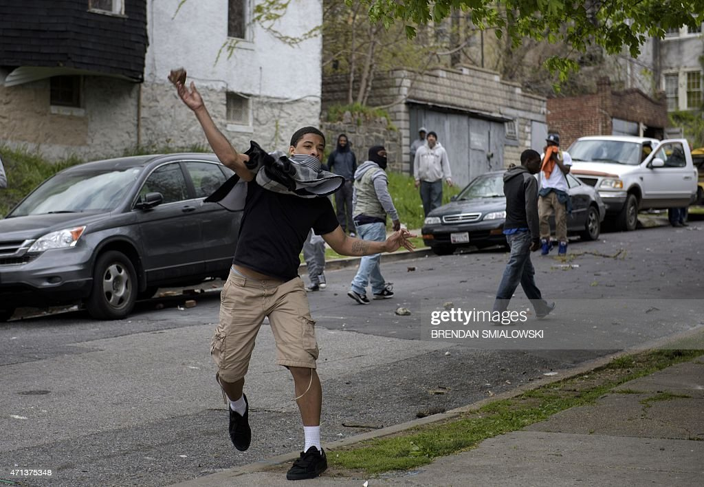 A youth throws a rock at police on April 27 2015 in Baltimore Maryland Violent street clashes erupted in Baltimore after friends and family gathered...