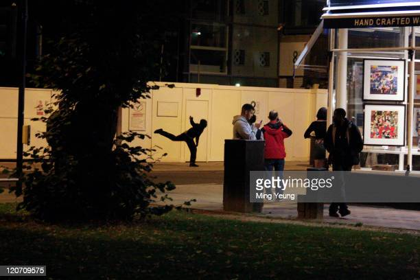 A youth throws an object in while protesting in the streets of Ealing on August 8 2011 in London England Sporadic looting and clashes with police...