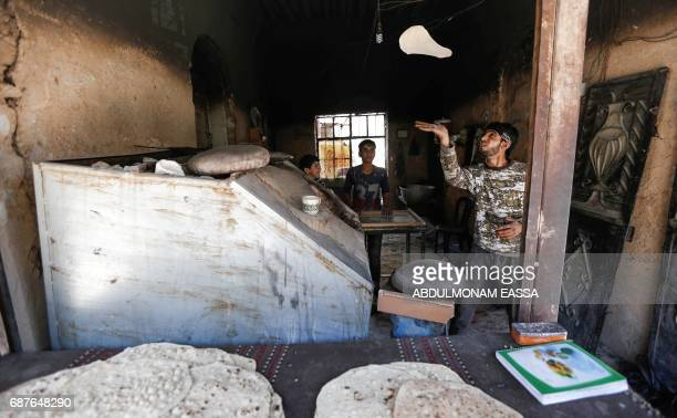 A youth tosses a bread dough at a bakery in the rebelcontrolled town of Hamouria in the eastern Ghouta region on the outskirts of the capital...