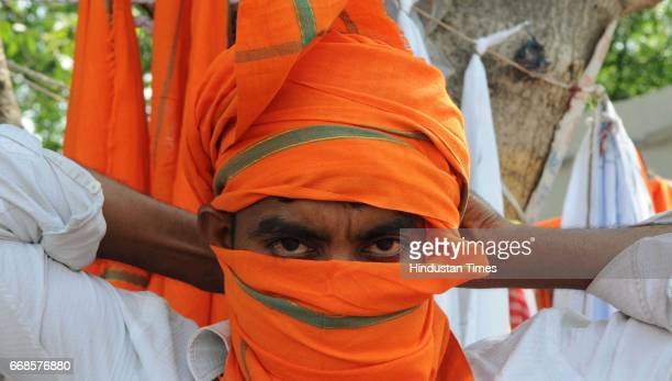 Youth tying saffron color cloth on his mouth on April 13 2017 in Lucknow India After the thumping victory of Bharatiya Janata Party in assembly polls...