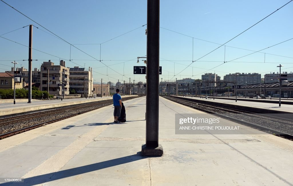 A youth waits for a train at the Saint Charles train station during a strike by French SNCF railway company employees on June 13, 2013, in Marseille. The strike was called by unions hostile to reforms of the train services sector recently proposed by the French government on May 29.