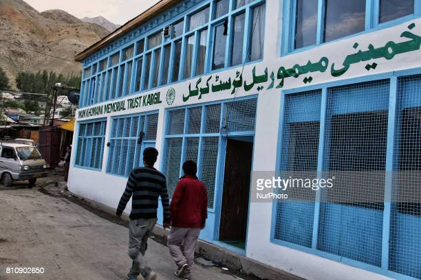Youth walk past the Imam Khomeini Memorial Trust in the town of Kargil Ladakh Jammu and Kashmir India