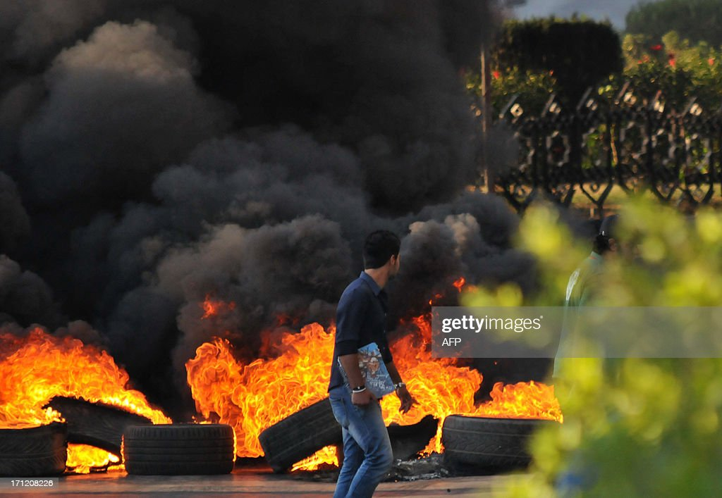 A youth walks past burning tires across a street in the northern city of Tripoli, on June 23, 2013, during protests in support of Sunni Muslim Sheikh Ahmad al-Assir whose supporters have clashed with the Lebanese army in the southern Lebanese city of Sidon. Two Lebanese army officers and a soldier were killed in the clash with supporters of the radical Sunni Muslim Sheikh opposed to the powerful Shiite movement Hezbollah, an army statement said.
