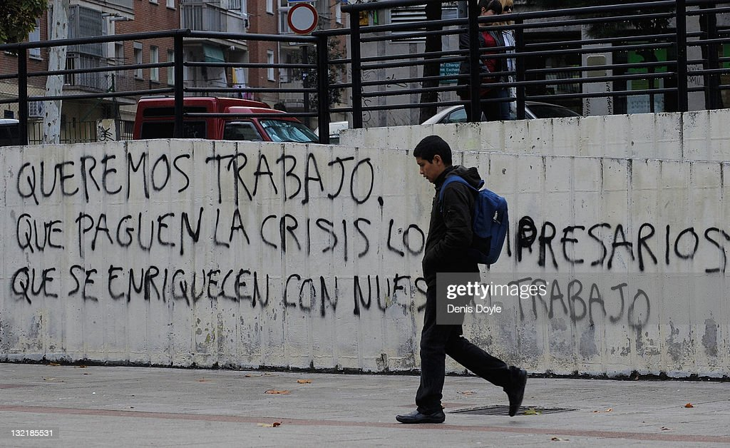 A youth walks past graffitti which reads 'We want to work, let the businessmen who have got rich from our labour pay for the crisis' on November 10, 2011 in Madrid, Spain. The current Eurozone debt crisis has left Spain with crippling economic problems. Mounting debts, record unemployment figures and the recent credit rating downgrade is leaving the country facing further economic stagnation. The people of Spain are preparing to go to the polls for a general election which will be held on November 20, 2011