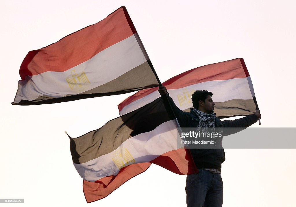 A youth waves Egyptian flags from a lamp post in Tahrir Square on February 1, 2011 in Cairo, Egypt. The Egyptian army has said it will not fire on protestors as they gather in large numbers in central Cairo.