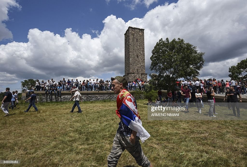A youth with a Serbian national flag draped around his shoulders walk past the Gazimestan memorial, near the village of Mazgit, Kosovo, as people take part in a ceremony marking the historic 'Battle of Kosovo', on June 28, 2016. The ceremony marks the Battle of Kosovo in 1389 when the Serbian army was defeated by the Ottoman Empire. / AFP / ARMEND