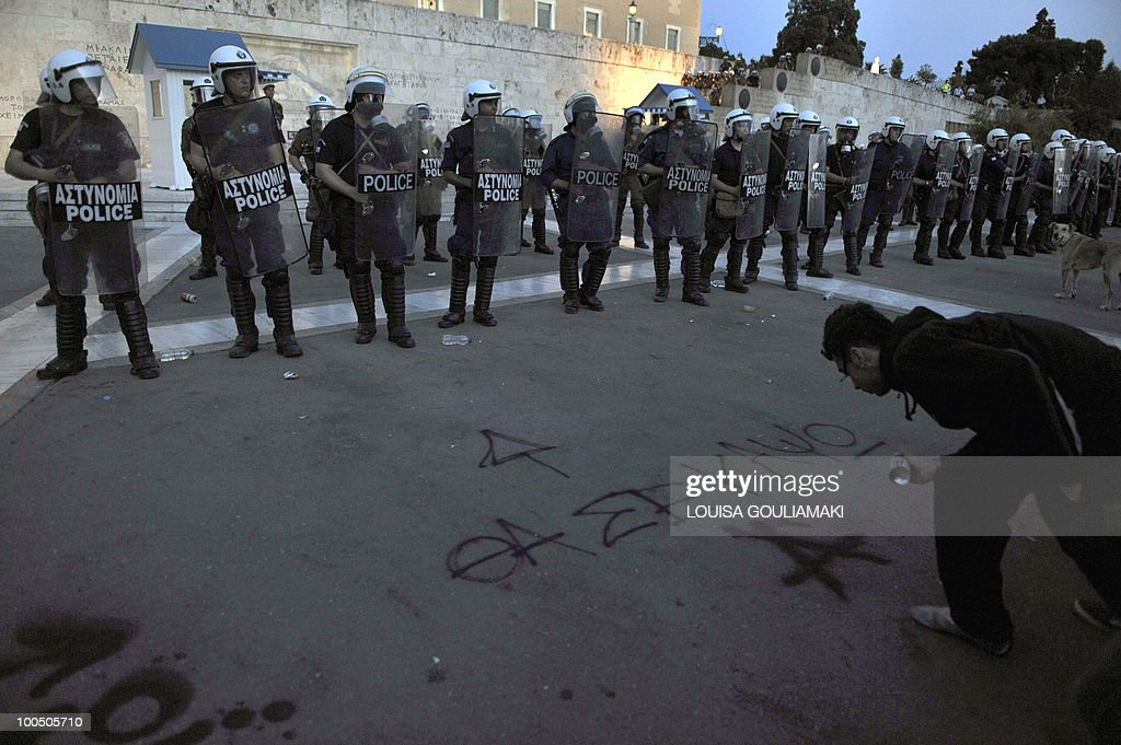 A youth writes 'I will burn you' below an arrow pointing at the greek Parliament during a protest there on May 6, 2010. More than 10,000 people demonstrated peacefully in Greek capital as lawmakers voted on a drastic austerity package, a day after protests against cutbacks degenerated into deadly riots, police said .
