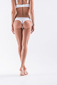 Close up of body of young slim girl in white set of bra and panties standing on toes. Focus on back. Isolated
