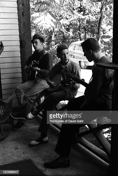 Youthful folk music enthusiasts play guitars and banjos in an impromptu hootenanny on a porchfront near the site of the Newport Folk Festival in July...