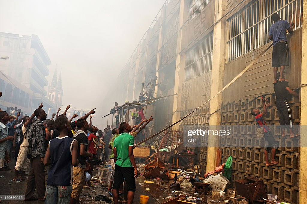 Youths attempt to use a fire hose to tear out a window to gain access to a smouldering hotspot in Lome's Grand Marche (''Big Market'') on January 12, 2013 after it was engulfed in flames late on January 11. Togolese firefighters were assisted by the Ghanaian Fire Department in battling the blaze. AFP Photo / Daniel Hayduk
