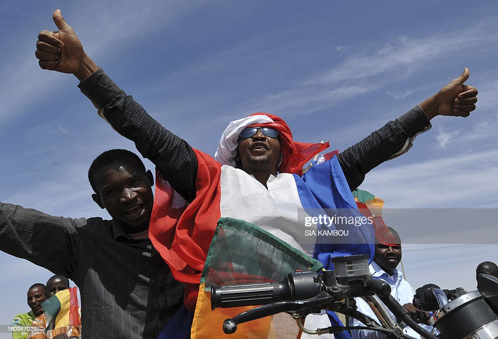 Youths celebrate with the French flag on January 29, 2013 in Ansongo, a town south of the northern Malian city of Gao, as Niger troops enter the city. Troops from Niger and Mali on january 29 entered Ansongo, which along with Gao was recaptured by French-led soldiers over the weekend in a lightning offensive against radicals holding Mali's north. So far, just 2,000 African troops have been sent to Mali or neighboring Niger, many of them from Chad, to boost the French-led offensive which began on January 11 and led to the recapture of several towns, including Ansongo.