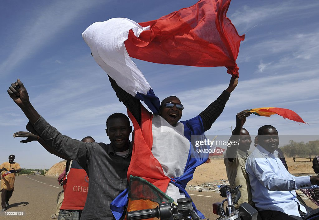Youths celebrate witht the French flag on January 29, 2013 in Ansongo, a town south of the northern Malian city of Gao, as Niger troops enter the city. Troops from Niger and Mali on january 29 entered Ansongo, which along with Gao was recaptured by French-led soldiers over the weekend in a lightning offensive against radicals holding Mali's north. So far, just 2,000 African troops have been sent to Mali or neighboring Niger, many of them from Chad, to boost the French-led offensive which began on January 11 and led to the recapture of several towns, including Ansongo. AFP PHOTO / KAMBOU SIA