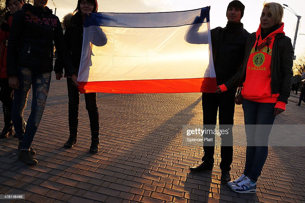 Youths hold a Crimean flag at a rally in support of the upcoming referendum on March 12, 2014 in Yevpatoria, Ukraine. As the standoff between the Russian military and Ukrainian forces continues in Ukraine's Crimean peninsula, world leaders are pushing for a diplomatic solution to the escalating situation. Crimean citizens will vote in a referendum on 16 March on whether to become part of the Russian federation.