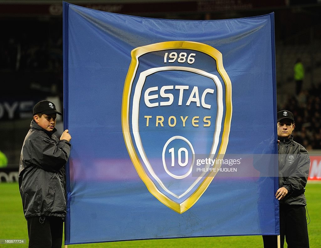 Youths hold a flag of Troyes (ESTAC) French football team before the French L1 football match Lille (LOSC) vs Troyes (ESTAC) on February 2, 2013 at the Grand Stade Stadium in Villeneuve d'Ascq. AFP PHOTO PHILIPPE HUGUEN
