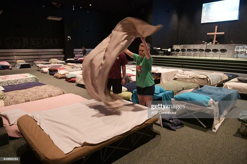 TOPSHOT - Youths in a shelter for volunteer rescue workers set up at the Fairfield Baptist Church student building on August 29, 2017 in Cypress, Texas. The shelter was set up as a place for volunteer rescue workers who had come to the Houston area in the aftermath of Hurricane Harvey. Harvey has set what forecasters believe is a new rainfall record for the continental US, officials said Tuesday. Harvey, swirling for the past few days off Texas and Louisiana has dumped more than 49 inches (124.5 centimeters) of rain on the region. NGAN