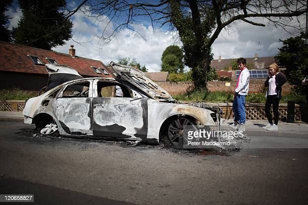 Youths look at the remains of a burnt out car in Enfield on August 8 2011 in London England Pockets of rioting and looting took place across some...