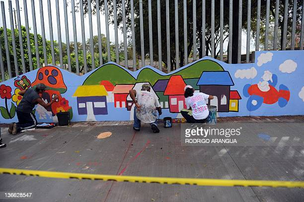 Youths paint murals on a street in Managua on January 9 2012 a day before Nicaraguan President Daniel Ortega of the Sandinista party is to be...