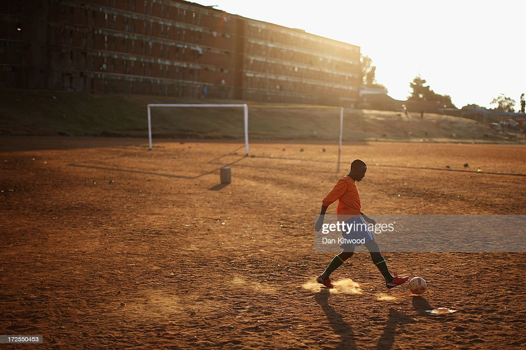 Youths play football in Alexandra township on July 1, 2013 in Johannesburg, South Africa. Anti-apartheid icon and Nobel Peace Prize laureate Nelson Mandela has been in hospital for three weeks where his condition has been described as 'critical but stable.'