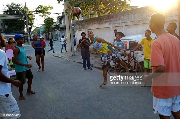 Youths play football in the Cidade de Deus shantytown in Rio de Janeiro Brazil on May 11 2013 AFP PHOTO/CHRISTOPHE SIMON